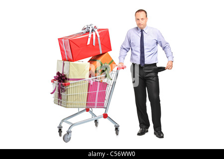 Man holding a shopping cart and gesturing no more money - Stock Photo