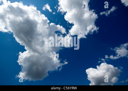 fluffy white clouds against a rich blue sky - Stock Photo