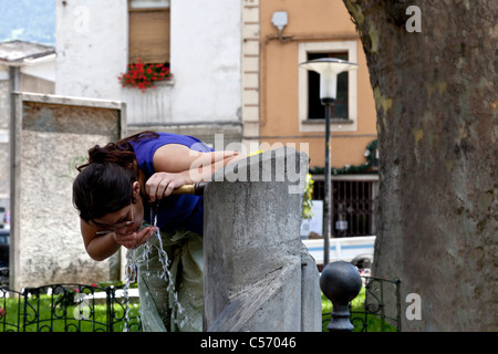 A young woman quenching her thirst at a fountain, in Aosta (Italy). Jeune femme étanchant sa soif à une fontaine - Stock Photo