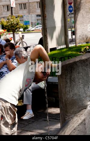 In Aosta, a young boy slaking his thirst at a fountain (Italy). Dans Aosta, jeune garçon étanchant sa soif à une - Stock Photo