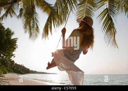 Woman swinging on tropical beach - Stock Photo