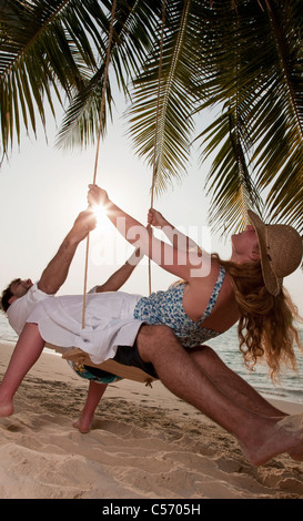 Couple playing on swing at beach - Stock Photo