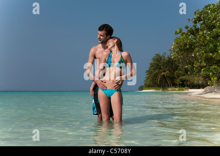 Couple hugging in water on beach - Stock Photo