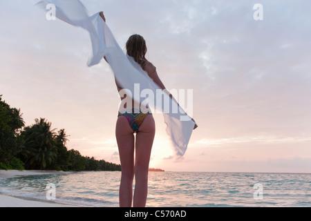 Woman holding towel on windy beach - Stock Photo