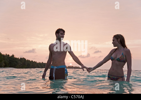 Couple holding hands in water at beach - Stock Photo
