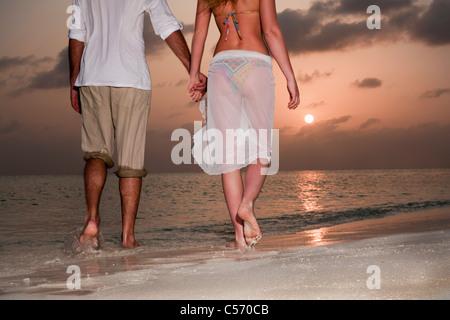 Couple walking hand-in-hand on beach - Stock Photo