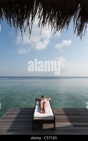 Woman laying on deck overlooking sea - Stock Photo