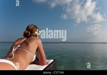 Woman laying on daybed overlooking sea - Stock Photo