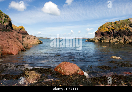 Waves gently breaking against a limpet covered red rock at North Haven Skokholm Island Pembrokeshire South Wales - Stock Photo