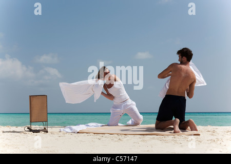 Couple having pillow fight on beach - Stock Photo