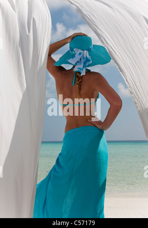 Woman on beach behind white curtains - Stock Photo