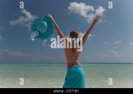 Woman cheering on tropical beach - Stock Photo