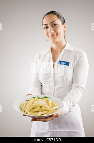 Woman in nametag holding plate of pasta - Stock Photo