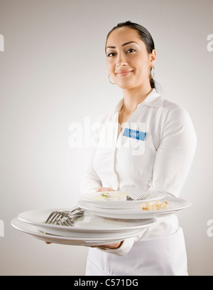 Woman in nametag carrying empty plates - Stock Photo