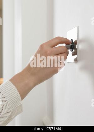 Woman turning on light switch - Stock Photo