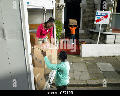 Family unpacking boxes from moving van - Stock Photo