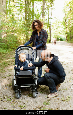 Family pushing baby in stroller - Stock Photo