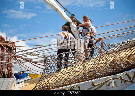 Men standing of the bowsprit of the Dar Mlodziezy, working on the rigging of a sail. Greenock, Scotland, UK - Stock Photo