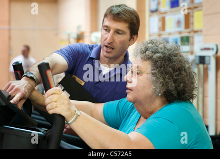 Trainer helping older woman exercise - Stock Photo