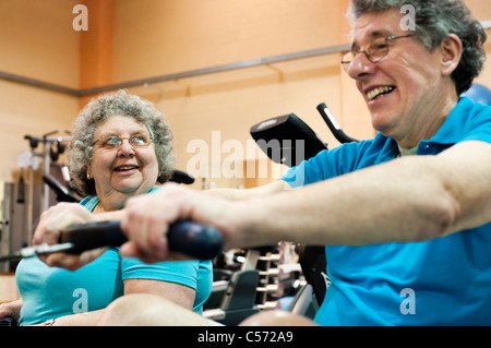 Older couple exercising in gym - Stock Photo