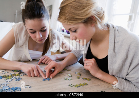 Teenage girls working on jigsaw puzzle - Stock Photo