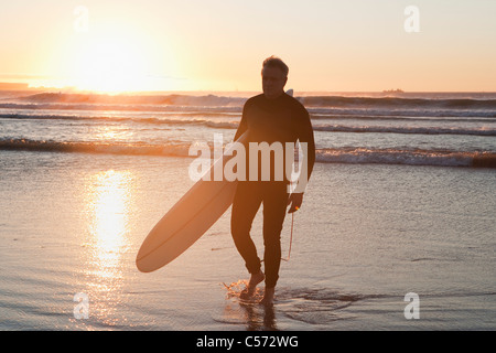 Surfer walking in water - Stock Photo
