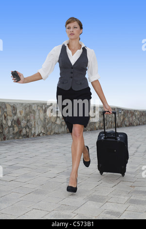 Businesswoman running with luggage - Stock Photo