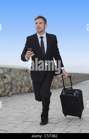 Businessman running with luggage - Stock Photo