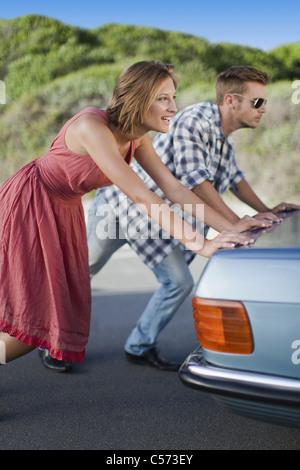 Couple pushing broken down car - Stock Photo