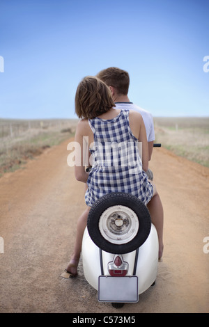 Couple riding scooter together - Stock Photo