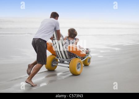 Man pushing girlfriend in cart on beach