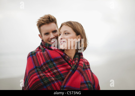 Couple wrapped in blanket on beach - Stock Photo