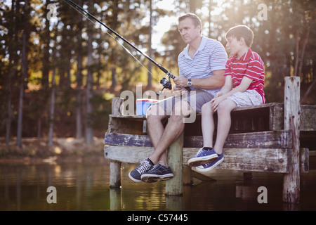 Father fishing with son in lake - Stock Photo