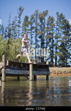 Boy jumping into lake from jetty - Stock Photo