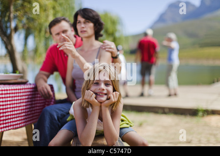 Young girl smiling at picnic bench - Stock Photo