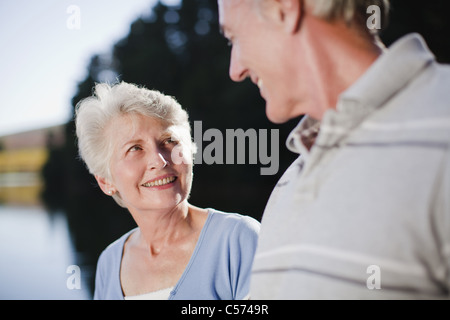 Smiling older couple talking outdoors - Stock Photo