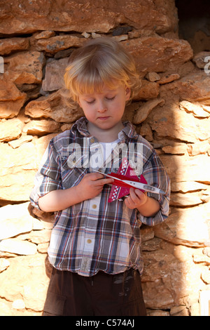 Boy playing with toy airplane outdoors - Stock Photo