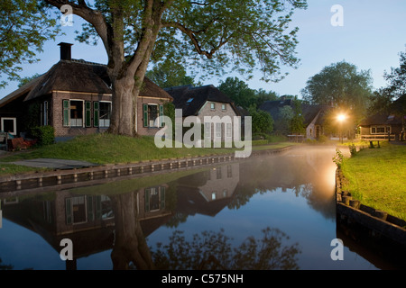 The Netherlands, Dwarsgracht, near Giethoorn. Village with almost only waterways. Houses at dawn. - Stock Photo