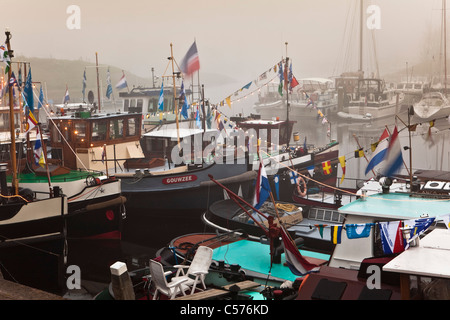 The Netherlands, Vollenhoven, Gathering of former towboats in harbour. Morning mist. - Stock Photo