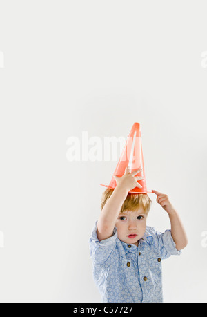 Toddler playing with traffic cone - Stock Photo