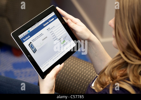 Close up picture of a young woman using Facebook social networking website on an iPad 2 - Stock Photo