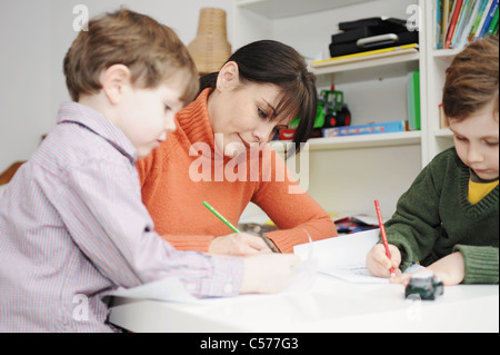 Mother and children drawing together - Stock Photo