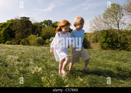 Children holding hands in field - Stock Photo