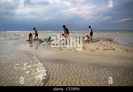 Children playing in the sand on a beach - Stock Photo