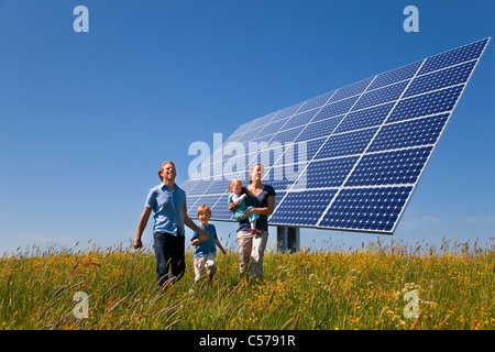 Family walking in field by solar panel - Stock Photo