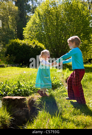 Boy helping sister cross creek - Stock Photo