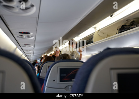 passengers onboard boarding an air canada embraer emb190 passenger aircraft waiting on man putting luggage in overhead - Stock Photo
