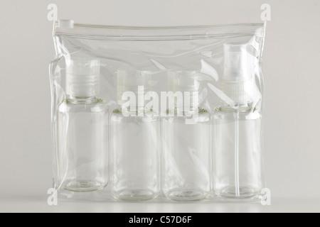 Four refillable plastic travel bottles - Stock Photo