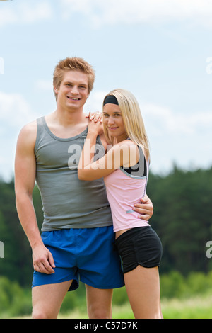 Sportive young couple happy posing in coutryside fit sportswear - Stock Photo