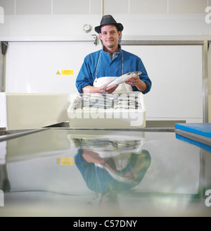 Worker packing mackerel in plant - Stock Photo